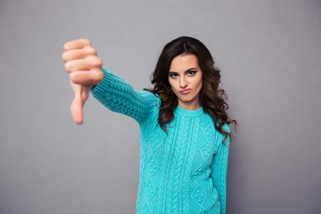 při pohledu na fotoaparát: Portrét mladé ženy ukazuje palcem dolů přes šedém pozadí