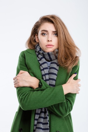Portrait of a young beautiful woman in coat and scarf freezing isolated on a white background Фото со стока