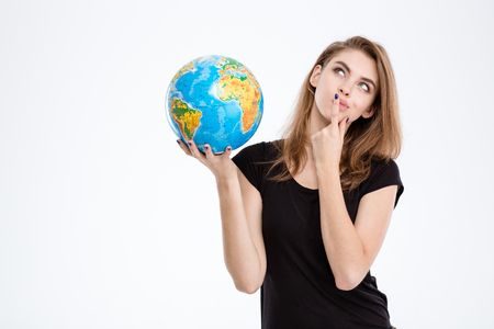 Portrait of a thoughtful woman holding world globe and looking up isolated on a white background
