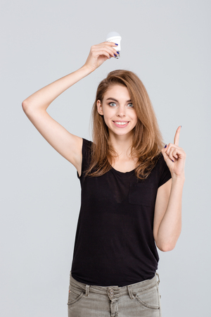 pointing finger up: Portrait of a happy young woman holding light bulb over head and pointing finger up isolated on a white background