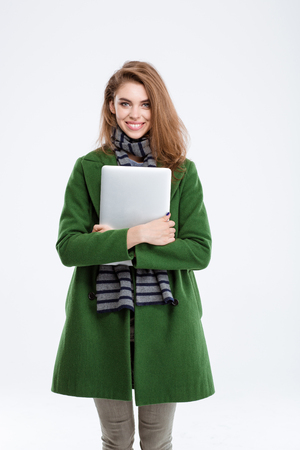 sports clothing: Portrait of a happy woman in green coat holding laptop and looking at camera isolated on a white background Stock Photo