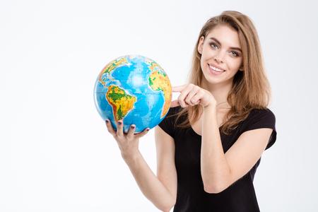 mundo manos: Retrato de una mujer sonriente que señala el dedo en el globo del mundo aislado en un fondo blanco