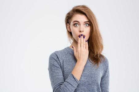 to gestures: Retrato de mujer sorprendido tap�ndose la boca con la palma de la mano aislado en un fondo blanco