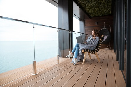 joven y bella mujer seria triste sentado envuelto en la colcha de punto gris en el gran balcón de cristal