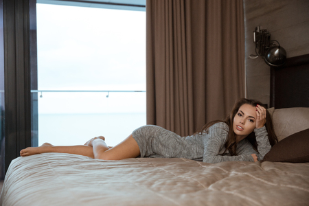 bedcover: Beautiful attractive young woman lying and relaxing on big bed in the room