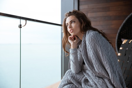 coverlet: Young beautiful woman sitting wrapped in gray knitted coverlet and thinking
