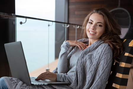 coverlet: Beautiful happy girl wrapped in knitted coverlet smiling using laptop