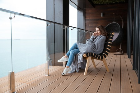 coverlet: Smiling young woman sitting wrapped in knitted coverlet on the glass balcony Stock Photo