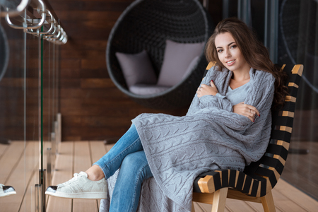 coverlet: Happy beautiful girl wrapped in gray knitted coverlet sitting on the chair on the balcony Stock Photo