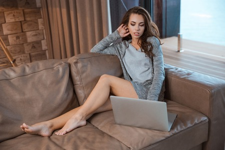 Young serious woman with long beautiful legs sitting on sofa and concentrate using the laptop Stock Photo