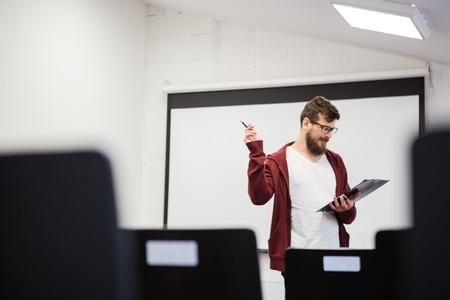 speaker: Handsome young speaker repeating his speech in empty classroom Stock Photo