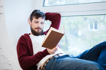 de vaqueros: Relajado chico joven y guapo en la sudadera con capucha de color marr�n y pantalones vaqueros que mienten en el alf�izar de la ventana y la lectura