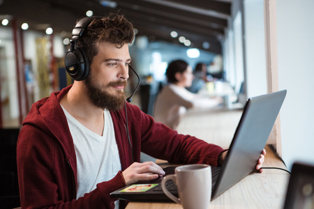 수염 사용하여 헤드셋과 노트북 집중 잘 생긴 남자 스톡 콘텐츠 - 48372515