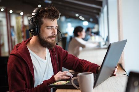 bel homme: Concentré beau mâle avec une barbe en utilisant un casque et un ordinateur portable Banque d'images