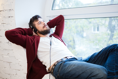 round window: Hansome young man dreaming lying and relaxing on white sill of round window