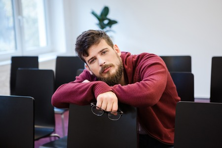 beau mec: Handsome guy with beard looking exhausted sitting in meeting room Banque d'images