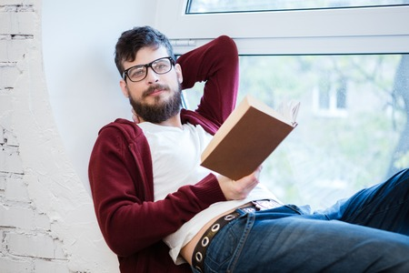 sill: Student with beard in glasses sitting on window sill and reading