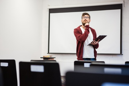 business training: Young modern teacher with beard preparing for the lecture in classroom