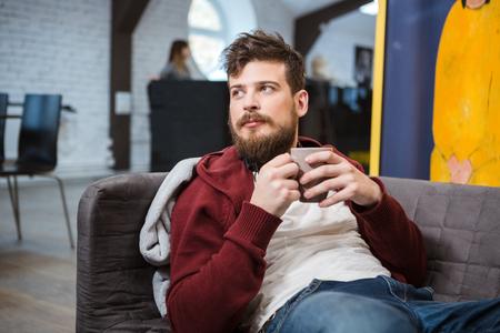 bel homme: Beau jeune homme allong� sur le canap� avec une tasse de th�