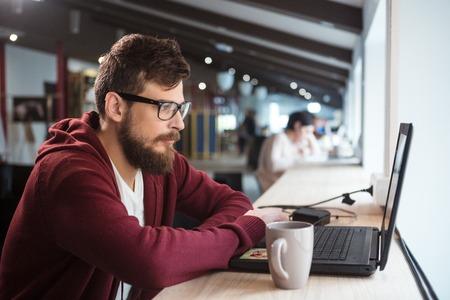 internet cafe: Hombre concentrado serio joven en gafas sentado en la oficina y el uso de ordenador port�til