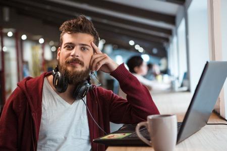 Jonge knappe zelfverzekerde knul in bruin hoodie werken in het kantoor met behulp van de headset en laptop