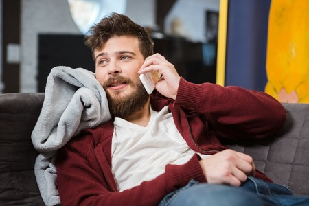 bedcover: Bearded young handsome guy lying on sofa and talking on cellphone Stock Photo