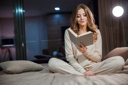 Mooie jonge krullende vrouw in pyjama op het bed en het lezen