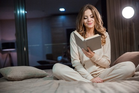 personas leyendo: Mujer rizada joven hermosa en pijama sentado en la cama y la lectura Foto de archivo
