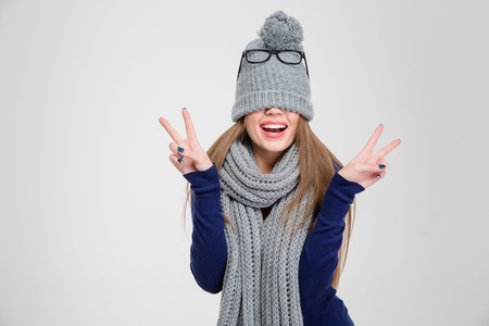 covering: Portrait of a happy woman covering her eyes with hat and showing peace sign isolated on a white background