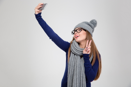 making faces: Portrait of a happy woman in winter cloth making selfie photo on smartphone and showing peace sign isolated on a white background Stock Photo
