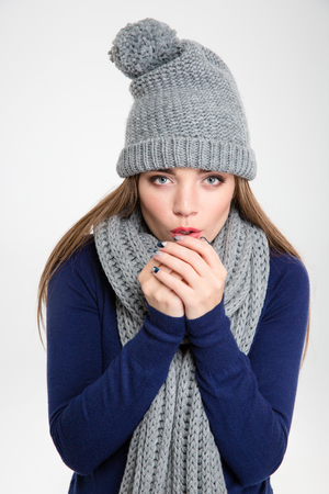 shiver: Portrait of a beautiful woman blowing in her hands when feeling cold isolated on a white background Stock Photo