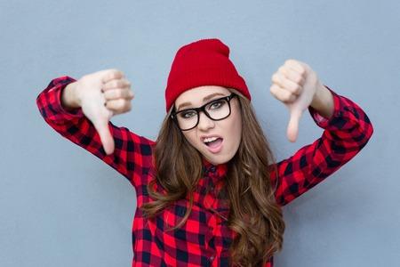 灰色の背景の上のジェスチャー親指を示す若い女性の肖像画 写真素材