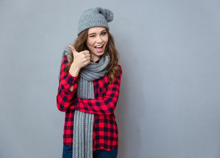 Portret van een vrolijke vrouw knipogen en het tonen van duim omhoog op een grijze achtergrond Stockfoto