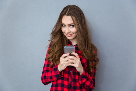 pretty: Portrait of a smiling pretty woman holding smartphone and looking at camera over gray background
