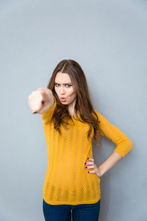 Portrait of a young woman pointing finger at camera over gray background Stock Photo