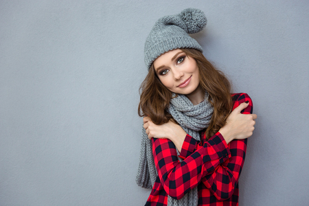 warm shirt: Portrait of a happy cute woman wearing in hat and scarf looking at camera on gray background