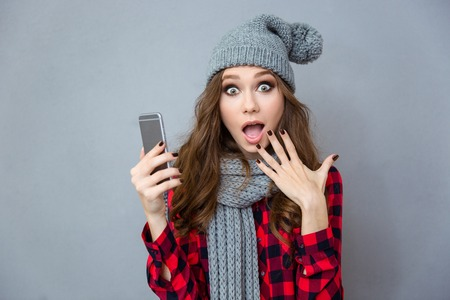 smartphone: Portrait of a shocked woman holding smartphone over gray background