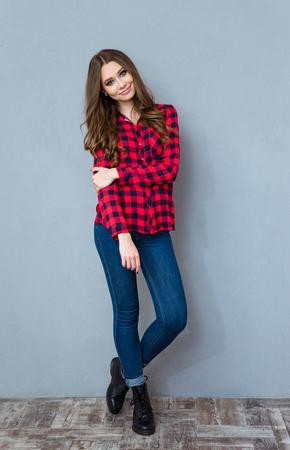 체크 무늬 셔츠와 청바지 포즈와 미소에서 젊은 예쁜 곱슬 여자 스톡 콘텐츠