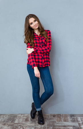 Young pretty curly woman in plaid shirt and jeans posing and smiling