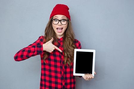회색 배경 위에 태블릿 컴퓨터 화면에 손가락을 가리키는 쾌활 힙 스터 여자의 초상화 스톡 콘텐츠