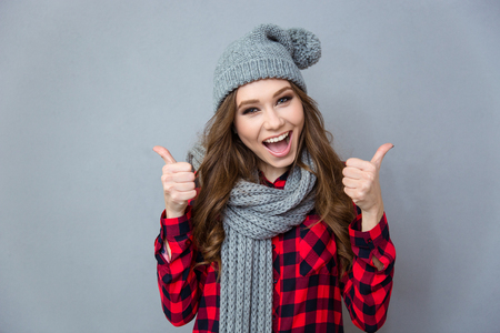 Portrait of a cheerful woman showing thumbs up over gray background