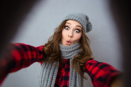 winter fashion: Portrait of a funny woman making selfie photo over gray background