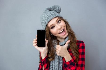 Portret van een vrolijke vrouw met blanco smartphone scherm en duim over grijze achtergrond Stockfoto