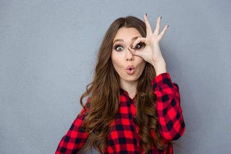 Grappig vermakelijke krullend meisje in geruit overhemd toont goed gebaar in de buurt van haar oog Stockfoto