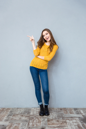 full shot: Full length portrait of a laughing woman pointing finger away on gray background