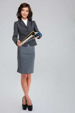 business costume: Pretty smiling curly young business woman in gray costume standing and holding folders with documents Stock Photo