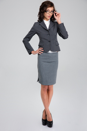 crossing legs: Concentrated confident curly pretty business woman in glasses and gray suit standing crossing legs and touching her glasses Stock Photo