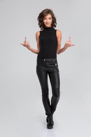 Vrij jonge krullende aantrekkelijke vrouw in zwart lederen broek en top blijkt onbeleefd gebaar met de middelvinger