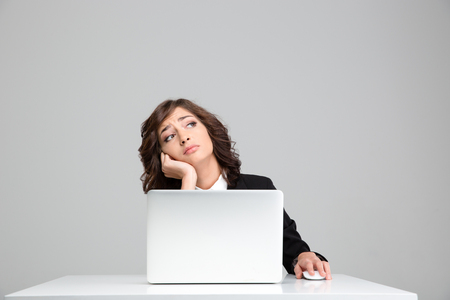 the thoughtful: Thoughtful sad depressed curly pretty business woman dreaming sitting at the laptop