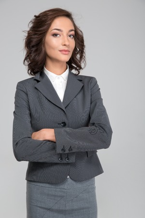 assured: Smug priggish assured successful young curly business woman in gray suit with arms crossed Stock Photo